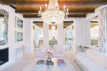 Освещенная люстра над роскошная гостиная — стоковое фото