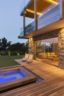 Modern house overlooking swimming pool and wooden deck — Stock Photo