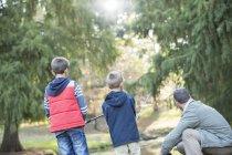 Padre e hijos juntos de pesca en el bosque - foto de stock