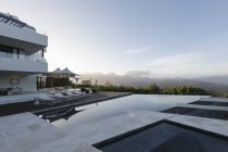 Tranquil modern luxury home showcase exterior with infinity pool and mountain view — Stock Photo