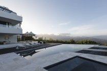 Спокійний сучасний розкішний будинок Вітрина зовнішній вигляд із пейзажним басейном і видом на гори — стокове фото
