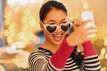 Mujer china juguetona con gafas en forma de corazón tomando selfie con el teléfono de la cámara - foto de stock