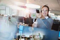 Empresária usando controle remoto, bebendo café no escritório — Fotografia de Stock