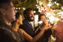 Друзья, играя с бенгальские огни на вечеринке — стоковое фото