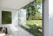 Modern house with glass walls overlooking grass — Stock Photo