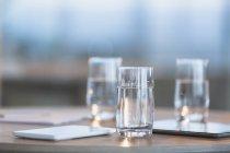 Вода в стаканах рядом с цифровыми таблетками на столе — стоковое фото