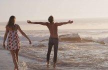 Jovem mulher assistindo exuberante jovem com braços estendidos no oceano surf — Fotografia de Stock