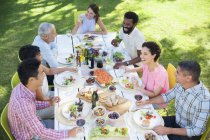 Friends talking at table outdoors — Stock Photo