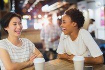Riendo a mujeres jóvenes tomando café en el café - foto de stock