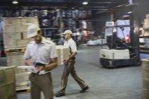 Trabalhadores que transportam e movem caixas com empilhadeira na doca de carregamento do armazém de distribuição — Fotografia de Stock