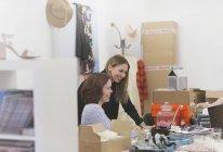 Modeeinkäufer arbeiten in chaotischem Büro am Laptop — Stockfoto