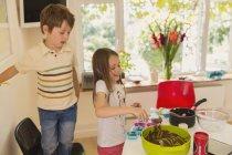 Jungen und Mädchen Bruder und Schwester machen Schokoladen Cupcakes in Küche — Stockfoto