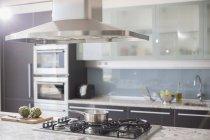 Olla en la estufa de gas en la cocina doméstica de lujo - foto de stock