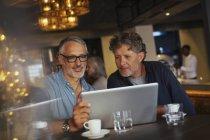 Men using laptop at restaurant — Stock Photo
