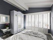 Quarto de luxo para casa vitrine com persianas de madeira brancas e tecto abobadado — Fotografia de Stock