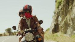 Junges paar Reiten Motorrad an sonnigen Straße — Stockfoto