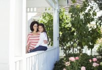 Portrait of smiling mother and daughter on porch — Stock Photo