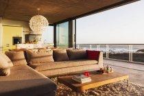 Диван и журнальный столик в современной гостиной с видом на океан — стоковое фото