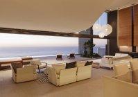 Sala de estar em casa moderna com vista para o mar ao pôr do sol — Fotografia de Stock
