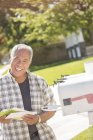 Portrait of smiling man retrieving mail from mailbox — Stock Photo