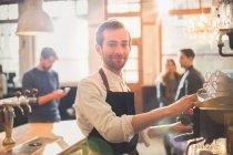 Портрет, улыбающееся мужского бариста с помощью эспрессо в кафе — стоковое фото
