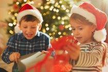Брат і сестра в Санта капелюхів відкриття Різдвяний подарунок — стокове фото