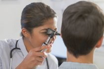 Female doctor using otoscope in ear of patient — Stock Photo