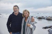 Ritratto sorridente coppia anziana che abbraccia sulla spiaggia tempestosa — Foto stock