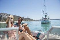 Pareja sentada en barco sobre el agua - foto de stock