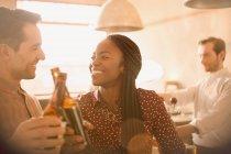 Lächelnde paar Toasten Bierflaschen in der Bar — Stockfoto