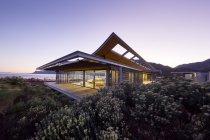 Современный роскошный дом с видом на океан в сумерках — стоковое фото