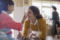 Mother and daughter playing in the kitchen — Stock Photo