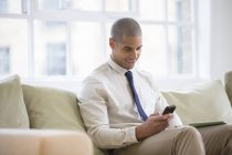 Businessman using cell phone on sofa at home — Stockfoto