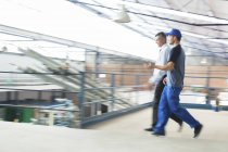 Supervisor and worker walking in food processing plant — Stock Photo