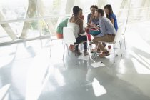 Creative business people meeting in circle of chairs — Stock Photo
