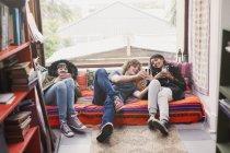 Junge Freunde, die Nutzung von Mobiltelefonen in Wohnung Fenster hängen — Stockfoto