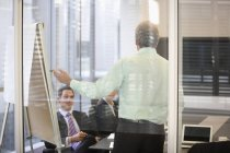 Businessman at flipchart in meeting at modern office — Stock Photo