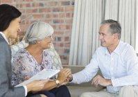 Financial advisor talking to couple on sofa — Stockfoto