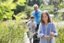 Girl carrying fishing rod in tall grass — Stock Photo