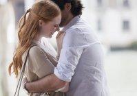 Улыбающаяся пара обнимается днем — стоковое фото
