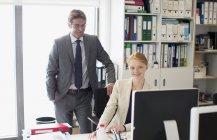 Uomo d'affari e donna d'affari che utilizzano il computer alla scrivania in ufficio — Foto stock
