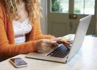 Mujer de compras en el ordenador portátil en interiores - foto de stock