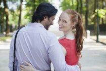 Retrato de mujer sonriente caminando con su novio en el Parque - foto de stock