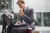 Uomo d'affari mangiare pranzo mentre si lavora fuori edificio per uffici — Foto stock