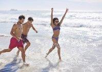 Восторженные друзья работает и плескались в океане — стоковое фото