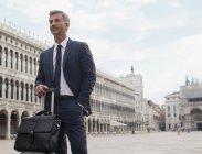Уверенный бизнесмен с портфелем и чемоданом на площади Святого Марка в Венеции — стоковое фото