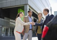 Business people shaking hands outdoors — Stock Photo