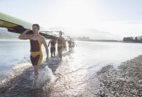Rowing crew carrying scull out of lake — Stock Photo