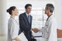 Лікар і бізнесмен рукостисканням в лікарні лобі — стокове фото