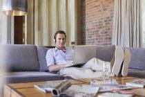 Man using laptop on sofa — Stock Photo